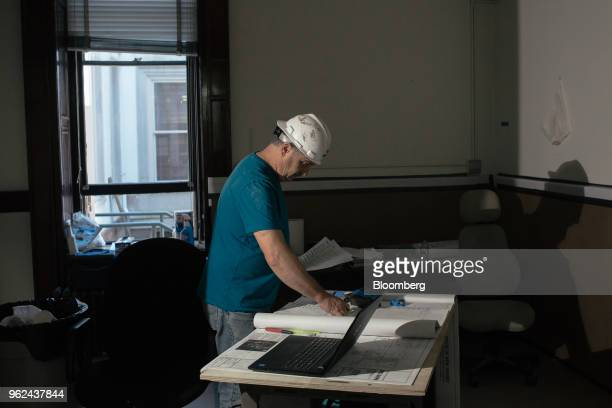A contractor views blueprints during renovations of the New Jersey State Capitol building in Trenton New Jersey US on Thursday May 14 2018...