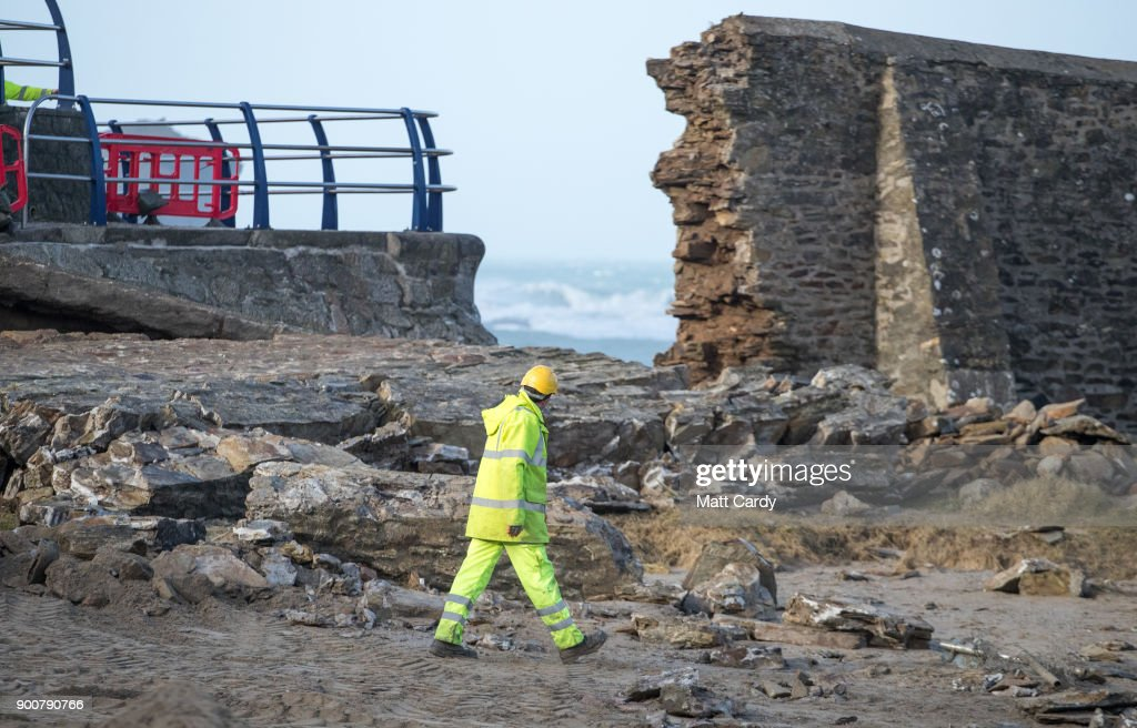 A contractor walks among the rubble strewn on the beach from the harbour wall that was damaged last night in Storm Eleanor in Portreath on January 3, 2018 in Cornwall, England. Overnight Storm Eleanor brought 70-100mph gusts and torrential rain to some parts of the UK and Ireland creating floods and cutting electricity supplies in some areas. A yellow warning by the Met Office is still in force.