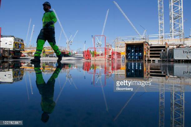 A contractor walks past a puddle reflecting construction work on the Hinkley Point C nuclear power station operated by Electricite de France SA near...