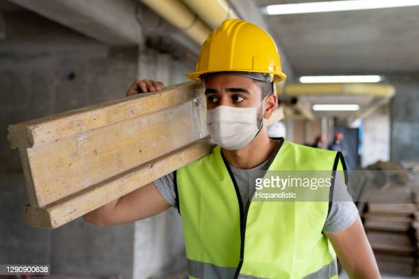 contractor wearing a facemask while working at a construction site carrying wood - biosecurity stock pictures, royalty-free photos & images