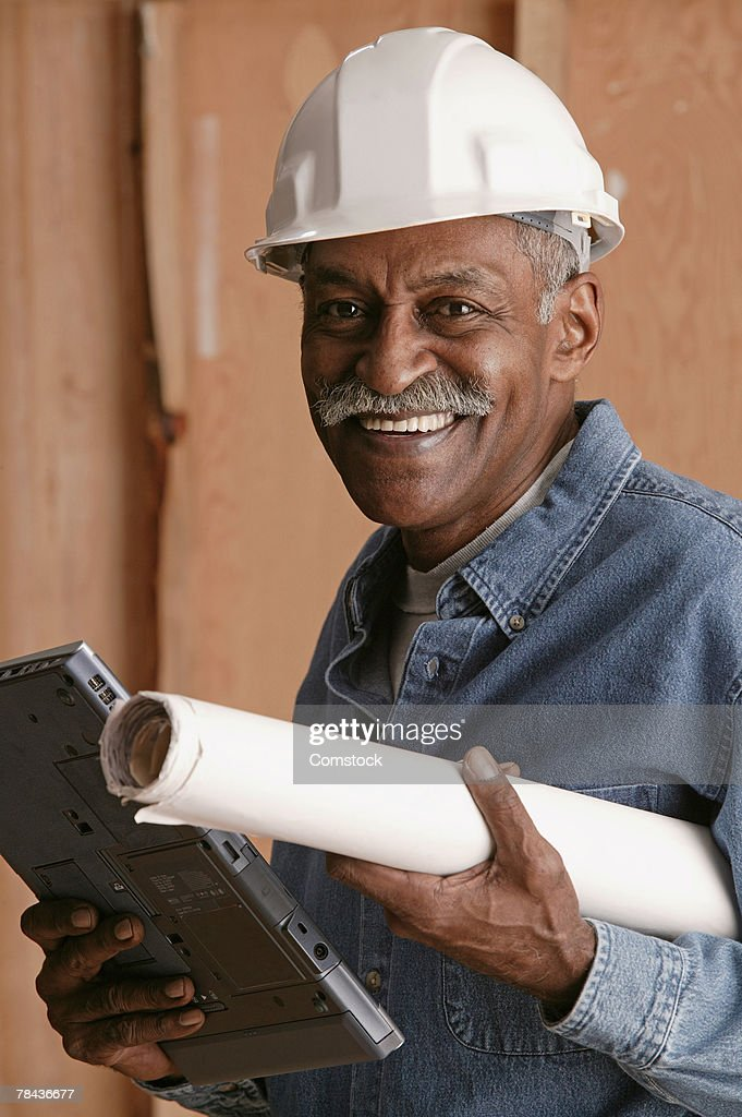 Contractor with blue prints and laptop computer : Stockfoto