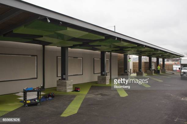 A contractor works on a new Amazoncom Inc drivethrough grocery location under construction in the Ballard neighborhood of Seattle Washington US on...