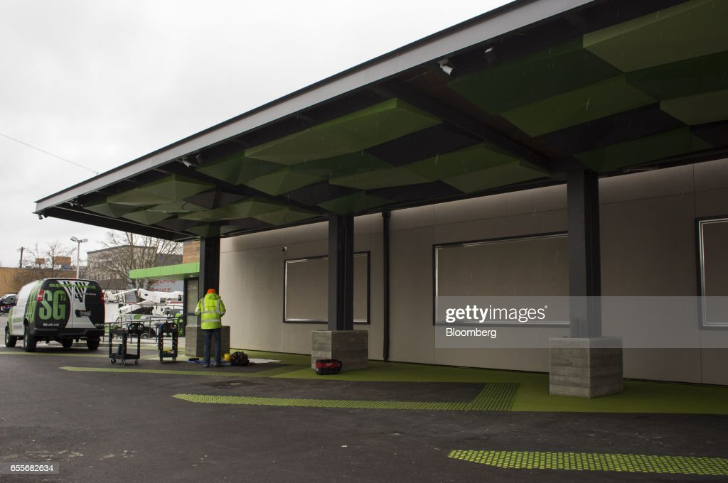 A contractor works on a new Amazon.com Inc. drive-through grocery location under construction in the Ballard neighborhood of Seattle, Washington, U.S., on Wednesday, March 8, 2017. Amazon's goal is to become a Top 5 grocery retailer by 2025, according to a person familiar with the matter. That would require more than $30 billion in annual food and beverage spending through its sites, up from $8.7 billion including Amazon Fresh and all other food and drink sales in 2016, according to Cowen & Co. Photographer: David Ryder/Bloomberg via Getty Images