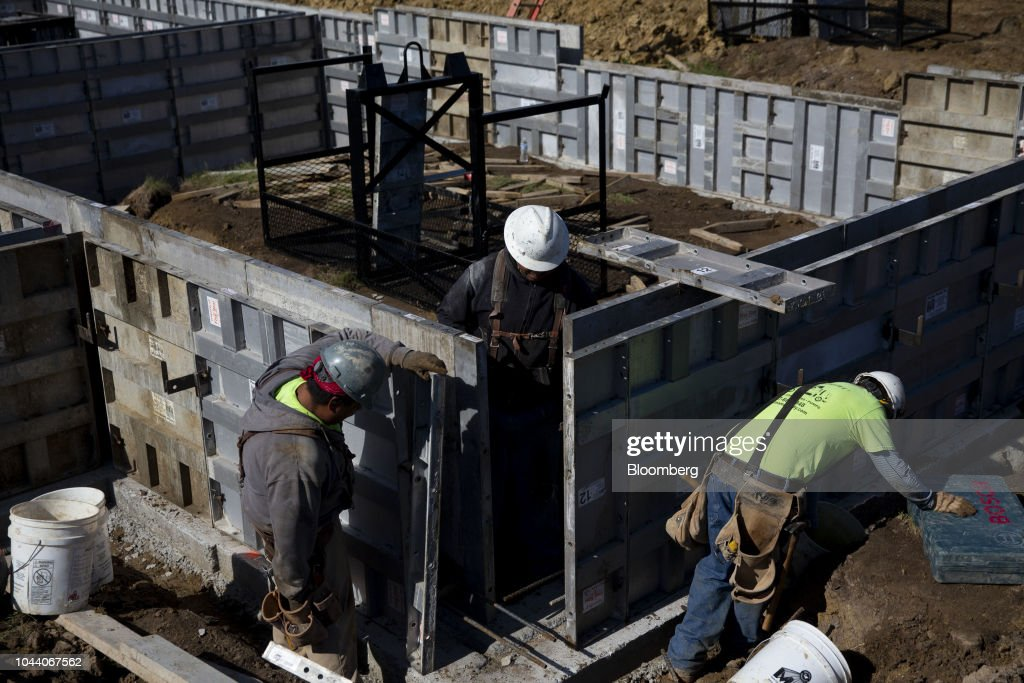 Contractors adjust concrete forms while working on a home under