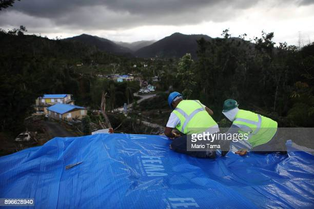 Contractors apply a FEMA tarp to a home damaged by Hurricane Maria and without electricity on December 20 2017 in Morovis Puerto Rico Barely three...