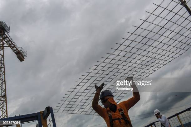Contractors carries a mesh reinforcement panel during construction at the Reserva Paulista residential complex in Sao Paulo, Brazil, on Wednesday,...