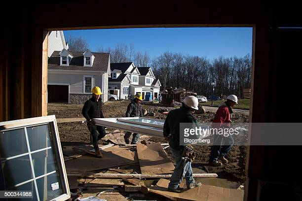 Contractors carry a sliding door to a home under construction at the Toll Brothers Inc Enclave at Rye Brook housing development in Rye Brook New York...