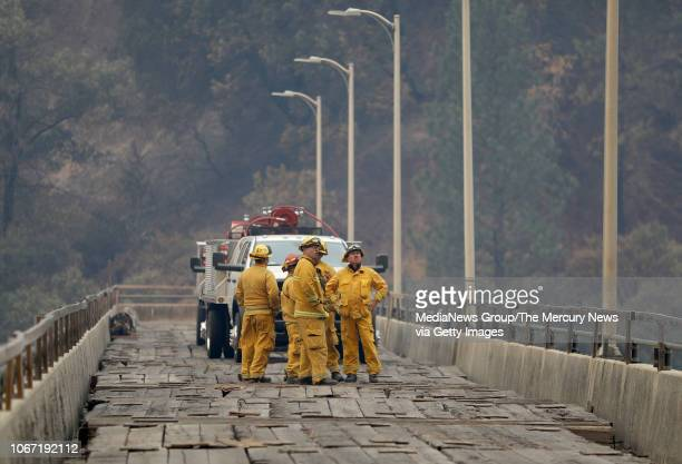 Contractors from Capstone Fire Management survey PG&E's Poe Power Dam in Pulga, Calif. Monday, Nov. 12 as the Camp Fire continues to burn nearby in...