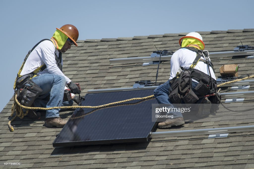 Contractors install SunRun Inc  solar panels on the roof of