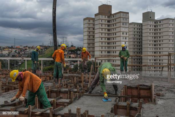 Contractors lay down cement during construction at the Reserva Paulista residential complex in Sao Paulo, Brazil, on Wednesday, March 21, 2018. The...