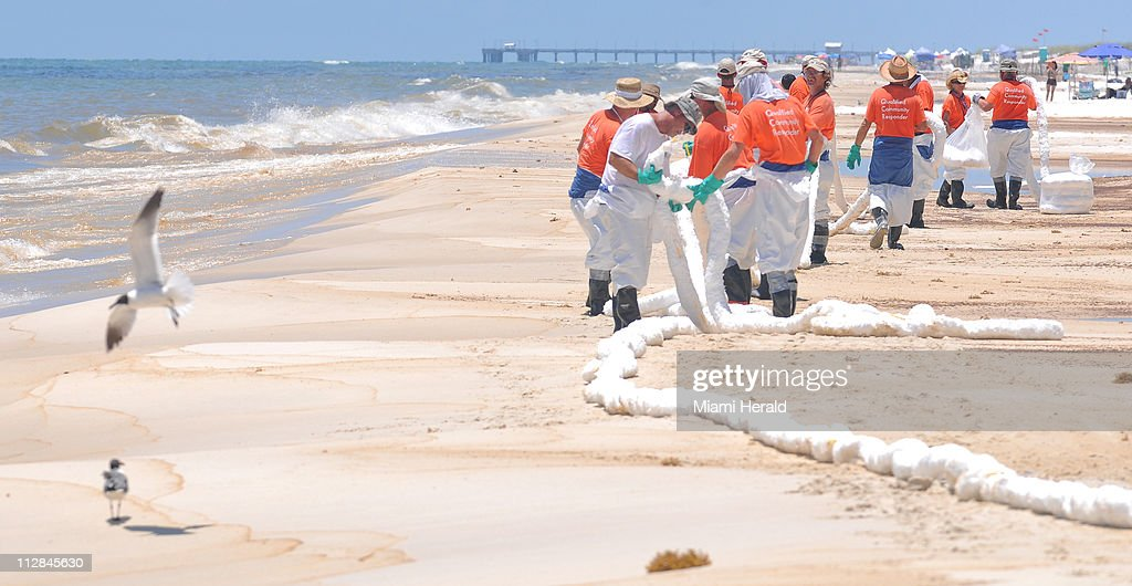 Contractors lay out absorbent boom on Orange Beach in Gulf Shores