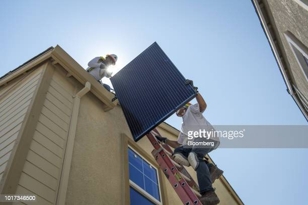 A contractor installs brackets for SunRun Inc solar panels on the roof of a new home at the Westline Homes Willowood Cottages community in Sacramento...