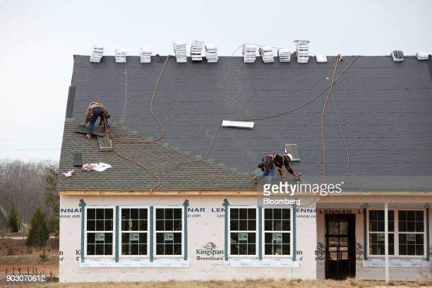 Contractors secure shingles to the roof of a house under construction at the Lennar Corp Tree Tops community development in Lancaster South Carolina...