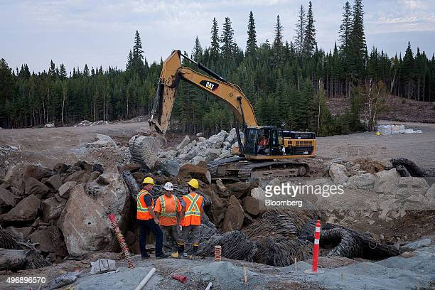Contractors stand next to a Caterpillar Inc machine during exploratory drilling and blasting at the Integra Gold Corp triangle zone in Val d'Or...