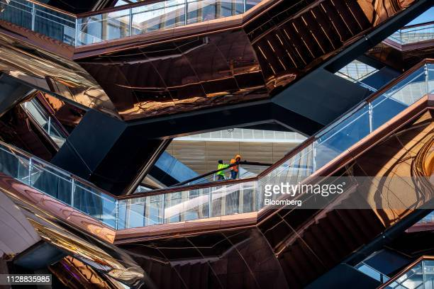 Contractors stand on a section of the Vessel sculpture by Thomas Heatherwick at the Hudson Yards development in New York US on Tuesday March 5 2019...