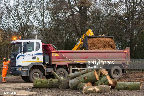 Contractors use a JCB 535-95 telehandler to load a truck with wood chip from mature trees recently felled around Grims Ditch for the HS2 high-speed...