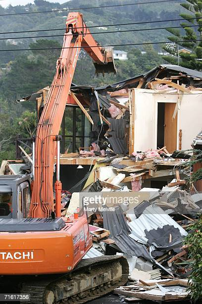 Contractors use an excavator to demolish one of the houses damaged by a landslide in the Lower Hutt City suburb of Kelson August 10 2006 in...