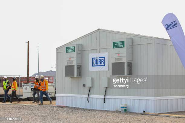 Contractors wearing protective masks walk past a trailer displaying Durr Systems AG signage at the Lucid Motors Inc. Manufacturing facility while...