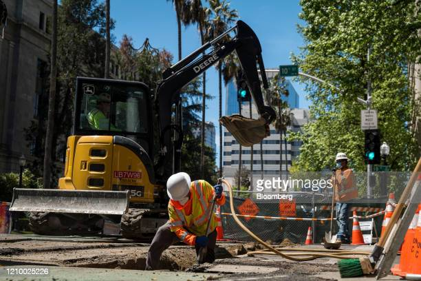 Contractors with Arrow Construction wearing protective masks work on a project in Sacramento, California, U.S., on Tuesday, April 14, 2020. Some of...