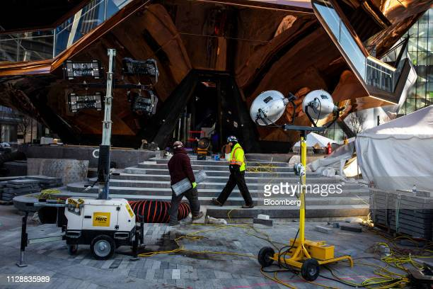 Contractors work in front of the Vessel sculpture by Thomas Heatherwick at the Hudson Yards development in New York US on Tuesday March 5 2019...