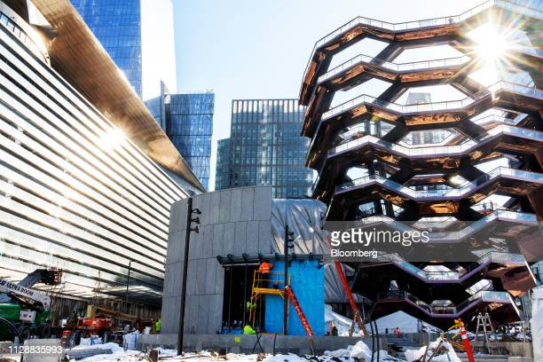 Contractors work near the Vessel sculpture by Thomas Heatherwick at the Hudson Yards development under construction in New York US on Tuesday March 5...
