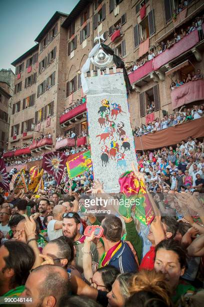 Contradaioli of Contrada Drago celebrte the victory of jockey Brio at the historical Italian horse race of the Palio Di Siena on July 02 2018 in...