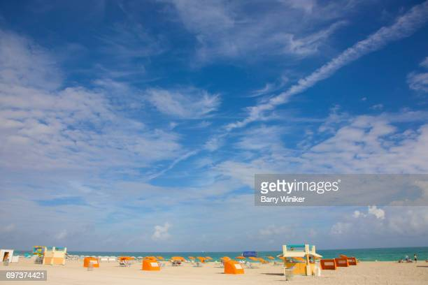 contrails in sky above miami beach, florida - miami dade county stock photos and pictures