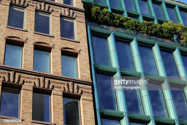 contrast between historical and modern buildings in bond street, noho, manhattan, new york city, usa - manhattan new york city stock pictures, royalty-free photos & images