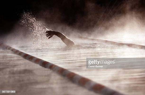 LSContrast3db06–25 As steam rises off the water an early morning swimmer swims through a heated pool in Reseda on a cold morning