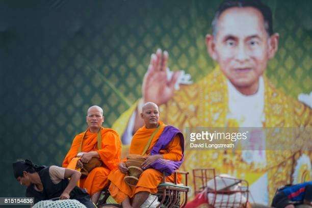 Contrasted against a giant billboard image of the late Thai King Bhumibol Adulyadej two Buddhist monks sit atop an elephant and look on during...