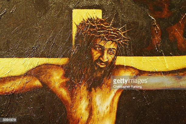 A contraversial painting portraying Christ on the cross with the face of Osama Bin Laden goes on display April 16 2004 in Irvine Scotland Artist Ryan...