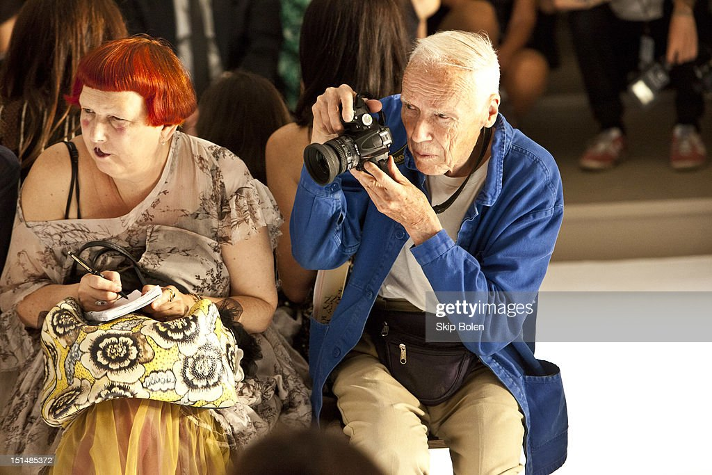 Contributing Fashion Editor for Vogue.com Lynn Yaeger and The New York Times fashion photographer Bill Cunningham watch a model on the runway at the Suno spring 2013 fashion show during Mercedes-Benz Fashion Week at Milk Studios on September 7, 2012 in New York City.