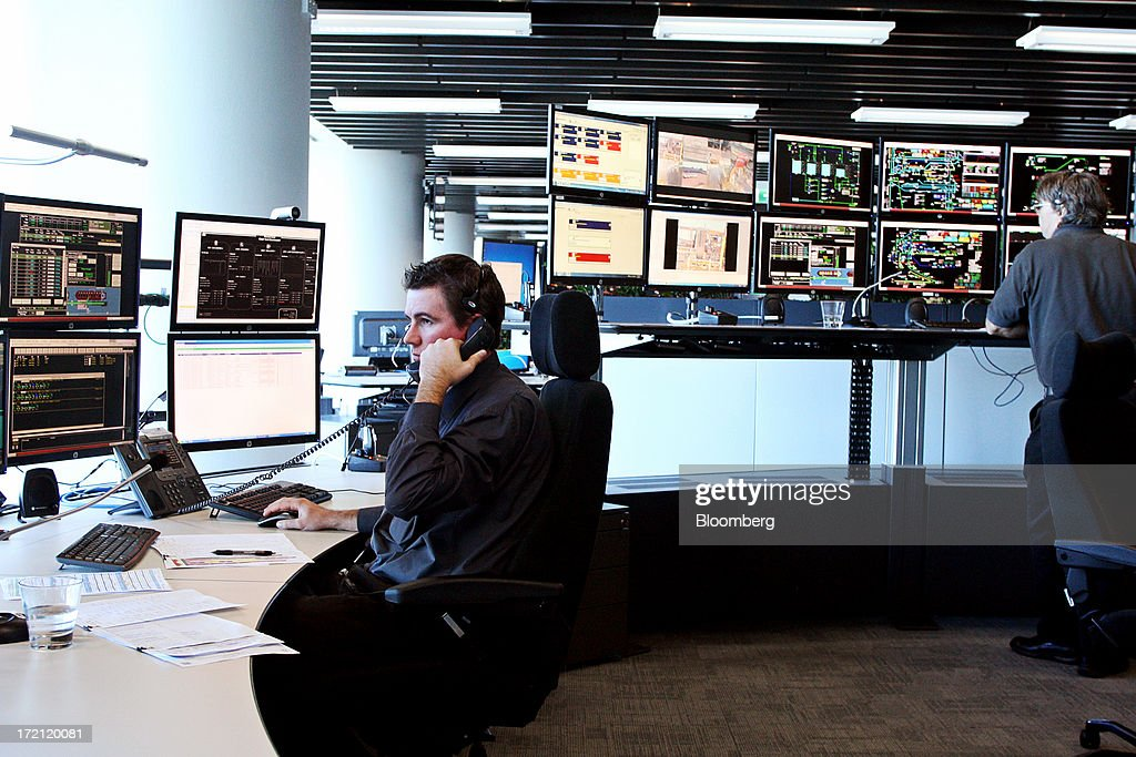 A control officer talks on the telephone as he and a colleague monitor the flow of iron ore from pit-to-port at BHP Billiton Ltd.'s new Integrated Remote Operations Center in Perth, Australia, on Tuesday, July 2, 2013. BHP Billiton is the world's largest mining company. Photographer: Sergio Dionisio/Bloomberg via Getty Images