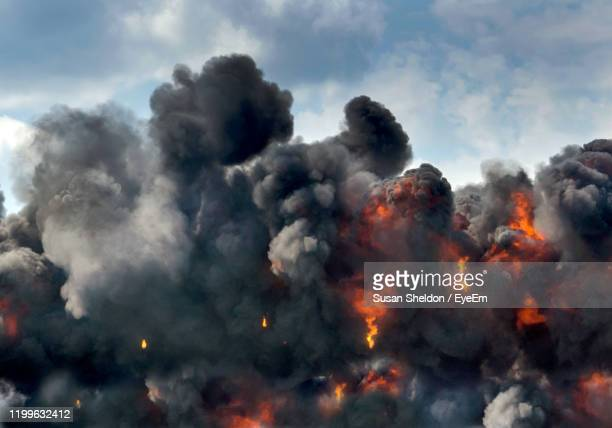 a controlled explosion is part of a war reenactment with fire and black clouds at an air show - war stock pictures, royalty-free photos & images