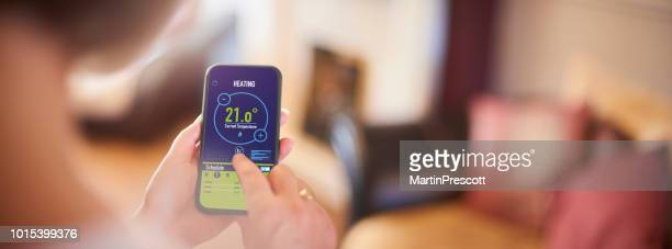 controlling home temperature on app - energy efficient stock pictures, royalty-free photos & images
