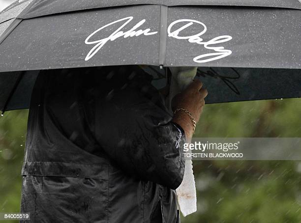 Controversial American golfer John Daly hides under his signature umbrella during the rainsoaked second round of the Australian Open at the Royal...