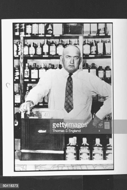 Controversial baseball player Shoeless Joe Jackson posing sternly by cash register of liquor store which he successfully ran after being ousted from...