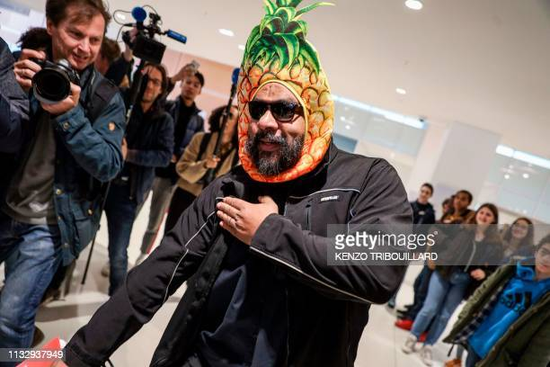 TOPSHOT Controversial French comic Dieudonne M'bala M'bala wearing a mask depicting a pineapple makes a controversial gesture named quenelle as he...