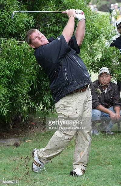 Controversial US golfer John Daly hits a penalty shot after smashing a fan's camera against a tree during the opening round of the Australian Open at...