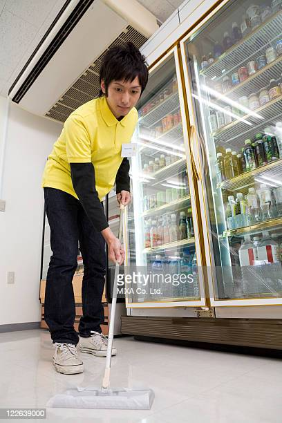 Convenience store clerk cleaning up store