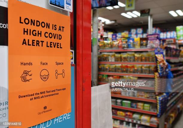 """Convenience store displays a sign informing customers that London is at a """"High"""" Covid alert level in the Soho district of London on October 18 as..."""