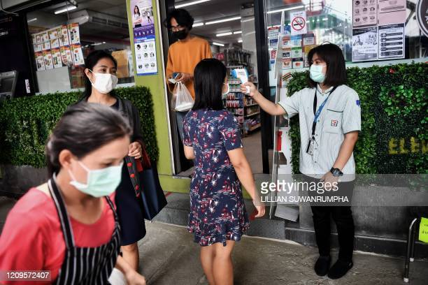 TOPSHOT A 711 convenience store employee takes the temperature of a customer in an effort to contain the spread of the COVID19 coronavirus in Bangkok...