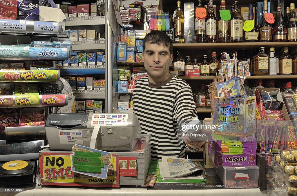 Convenience store owner handing over cigarettes. : Photo