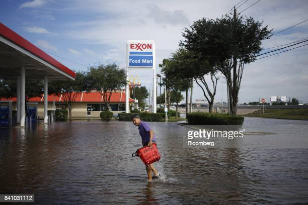 A convenience store owner walks through floodwaters from Hurricane Harvey outside an Exxon Mobil Corp gas station in Houston Texas US on Wednesday...