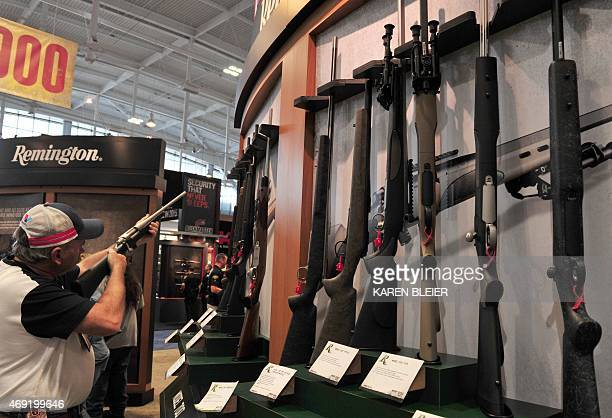 A convention attendee looks at a Remington bolt action rifle at the 2015 NRA Annual Convention in Nashville Tennessee on April 10 2015 The annual NRA...