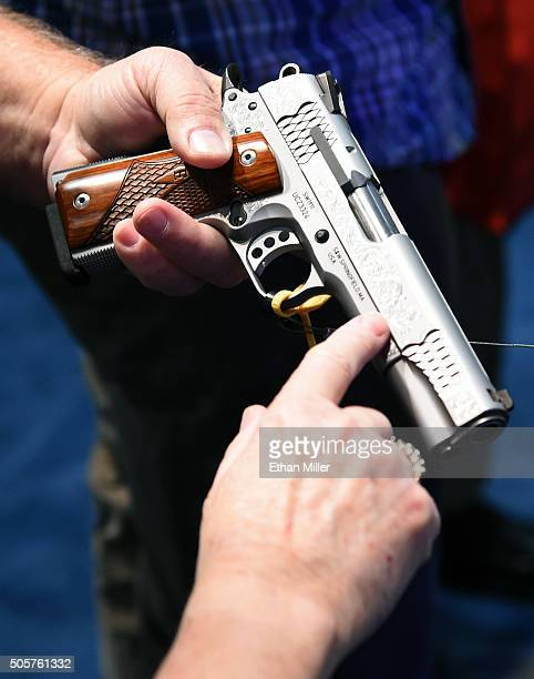 Convention attendees look at a model SW1911 Pro Series 9mm handgun at the Smith Wesson booth at the 2016 National Shooting Sports Foundation's...
