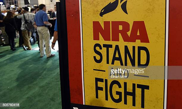 Convention attendees pass by a sign for the National Rifle Association at the 2016 National Shooting Sports Foundation's Shooting Hunting Outdoor...