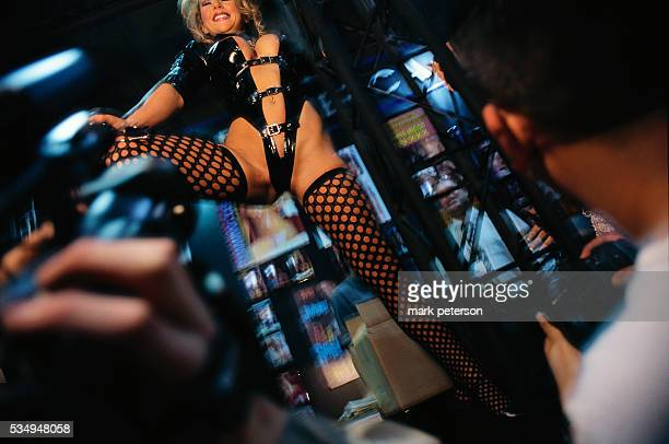 Convention attendees watch an exotic dancer at AdultDex an adult entertainment convention that runs along with the Consumer Electronics Show in Las...