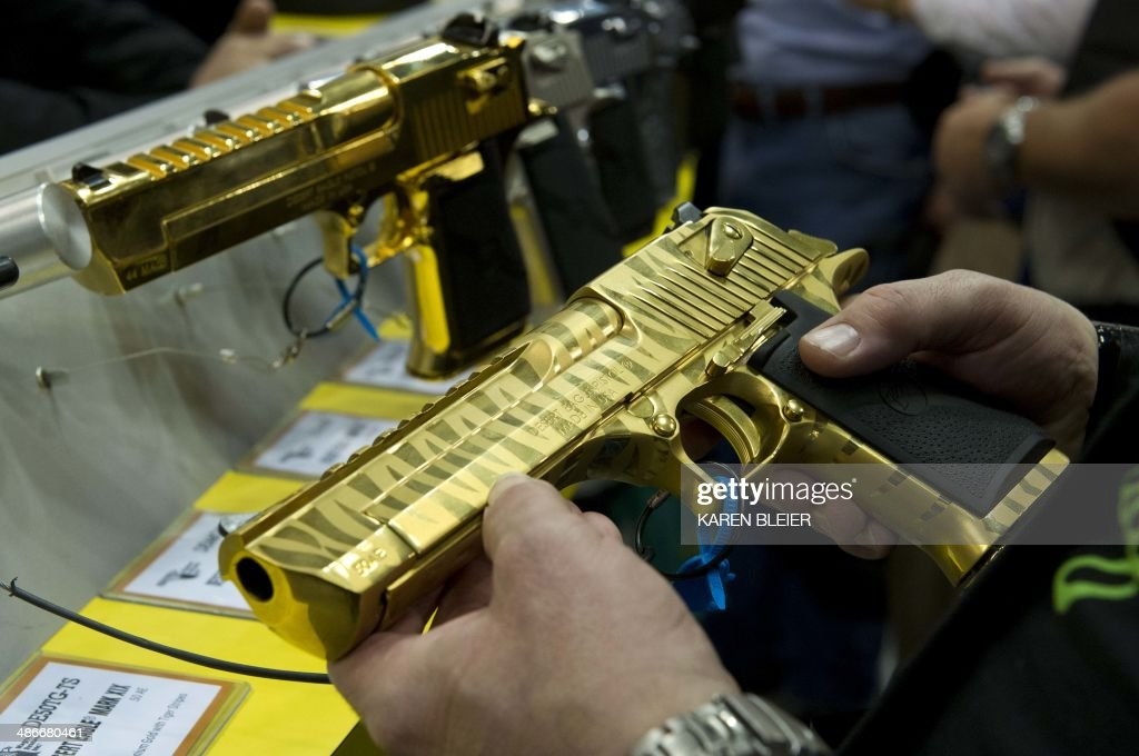 A convention goer holds a 24 karat gold plated Desert Eagle pistol