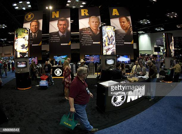 Convention goers walk through the NRA booth at the143rd NRA Annual Meetings and Exhibits at the Indiana Convention Center in Indianapolis Indiana on...